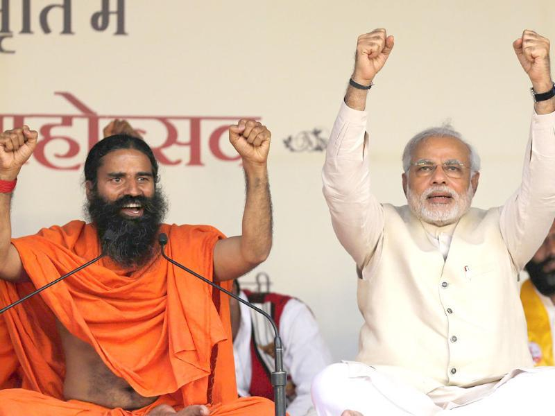 BJP prime ministerial candidate Narendra Modi and yoga guru Baba Ramdev raise their hands as they chant patriotic slogans during a Yoga Mahotsav or festival, in New Delhi. (Reuters)
