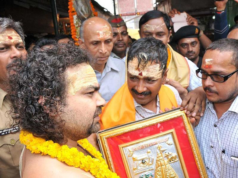AAP convener Arvind Kejriwal is presented a memento during his visit to the Kashi Vishwanath temple in Varanasi. HT Photo