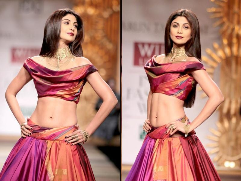 Actor Shilpa Shetty strutted down the catwalk amidst applause and hoots in a voluminous ghaghra skirt and off-shoulder cropped blouse at Tarun Tahiliani's autumn/winter 2014 collection at the Wills India Fashion Week. (HT Photo/ Raajessh Kashyap)