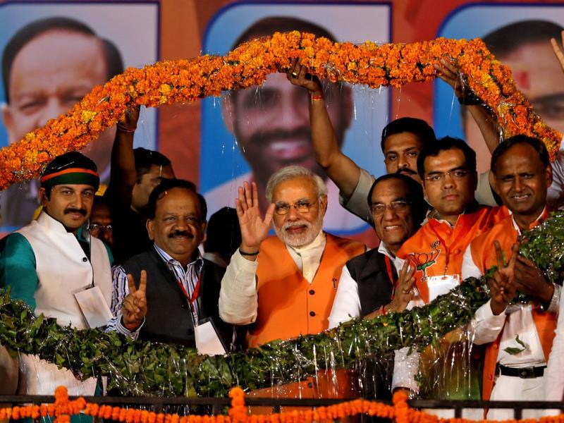 A giant floral garland is put around BJP PM candidate Narendra Modi, center, and other party leaders during an election rally in New Delhi. (AP Photo)