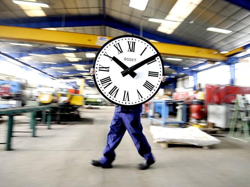 An employee of the Bodet Company carries a clock at the plant of Trementines, western France. The Bodet company manufactures clocks since 1868 for churches, stations, sports halls and employs 630 workers in France. (AFP photo)