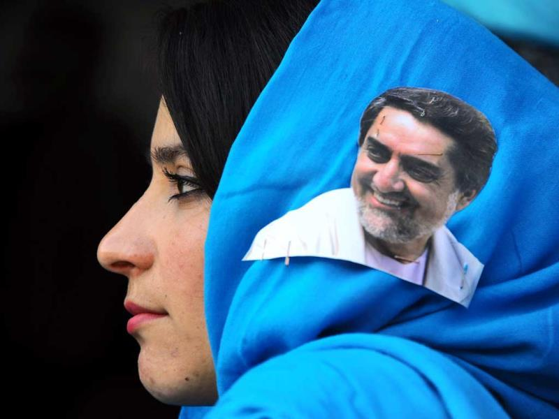 An Afghan woman with a portrait of presidential candidate Abdullah Abdullah on her scarf listens to his speech during a campaign rally in Herat. (AFP Photo)