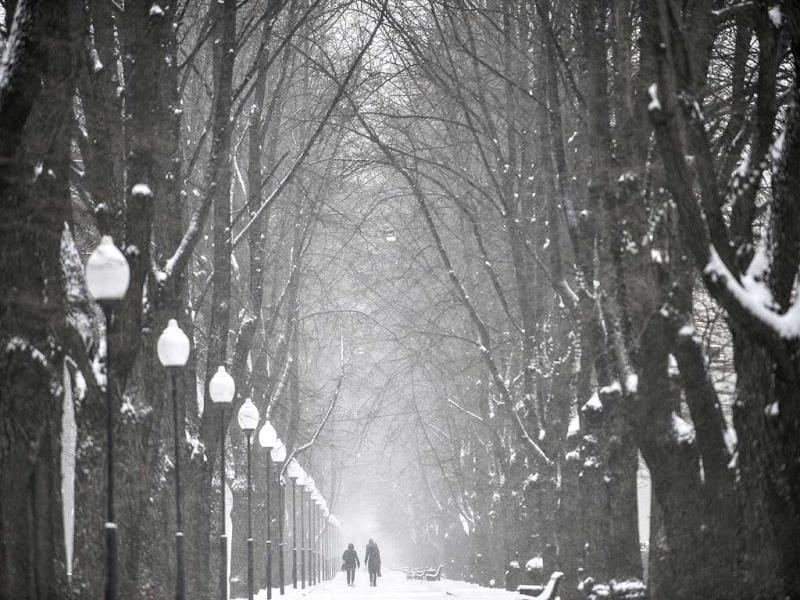 A couple walks through a snow covered park in Moscow, Russia. After a week of warm weather, temperatures plunged to -1 degrees Celsius (30 Fahrenheit) in Moscow. (AP Photo)