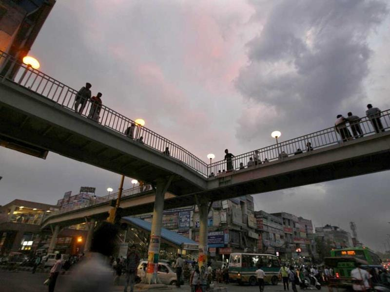 Daily commuters walking under dark clouds at Laxmi Nagar in New Delhi. (Raj K Raj/HT Photo)