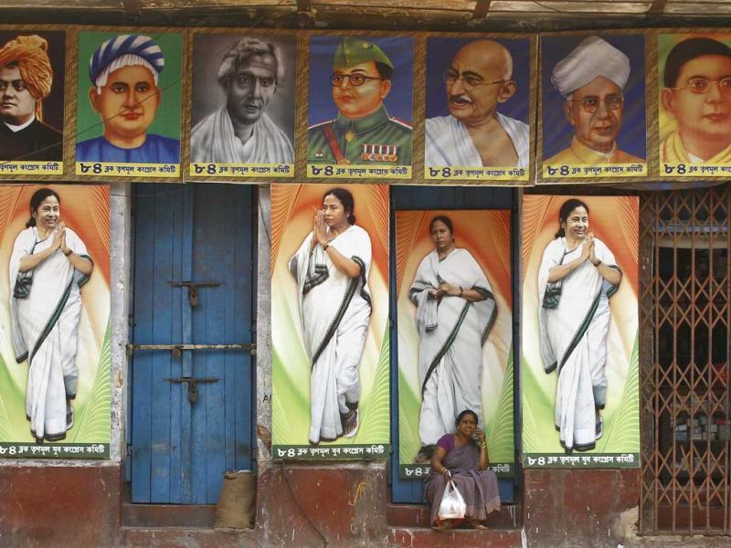 A woman speaks on a mobile phone as she sits under a building decorated with pictures of Mamata Banerjee, chief minister of West Bengal ahead of the general election in Kolkata. (Reuters)