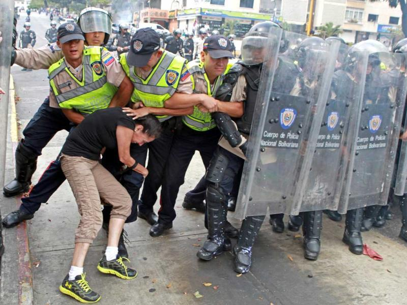 An anti-government activist clashes with riot police during a protest in Caracas. (AFP Photo)