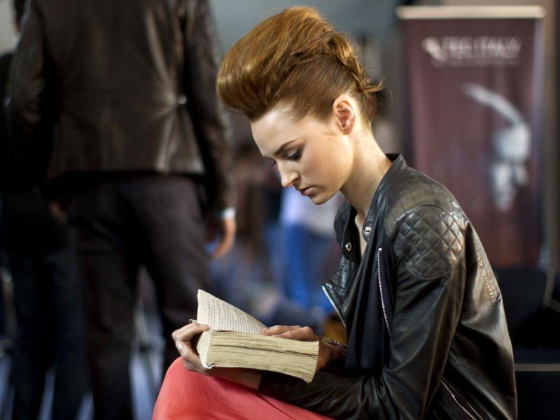 A model reads a book backstage before modeling the Alexia Ulibarri collection at Mexican Fashion Week in Mexico City. (AP)