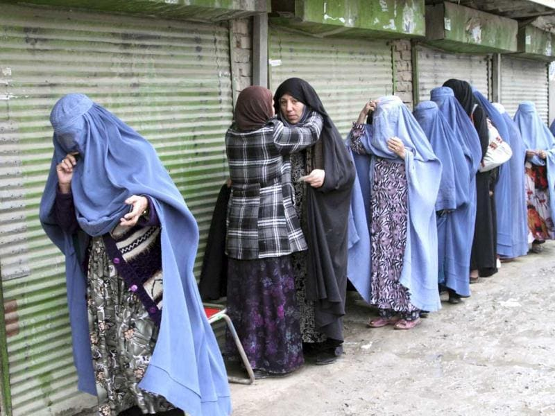 An Afghan woman searches voters before they enter a polling station to cast their ballots, in Kabul, Afghanistan. (AP Photo)