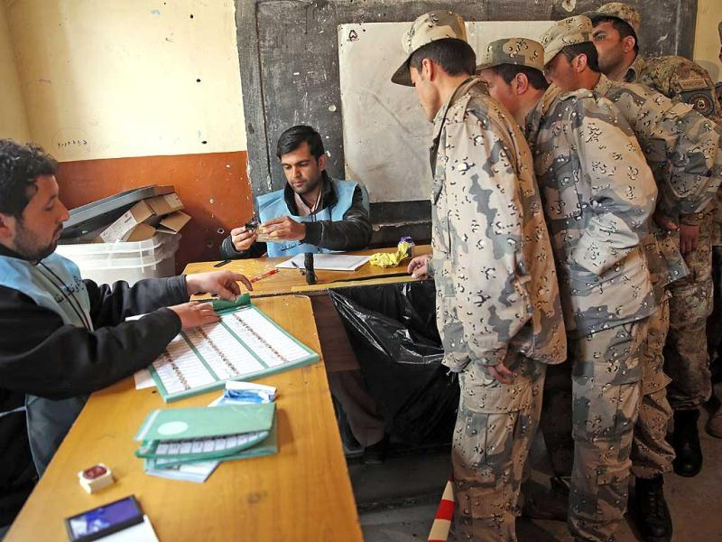 Afghan security personnel line up for the registration process before they cast their votes at a polling station in Kabul, Afghanistan. (AP Photo)
