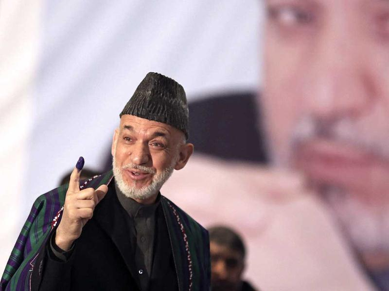 Afghan President Hamid Karzai shows indelible ink on his finger to the media before he casts his vote at Amani High School, near the presidential palace in Kabul. (AP Photo)