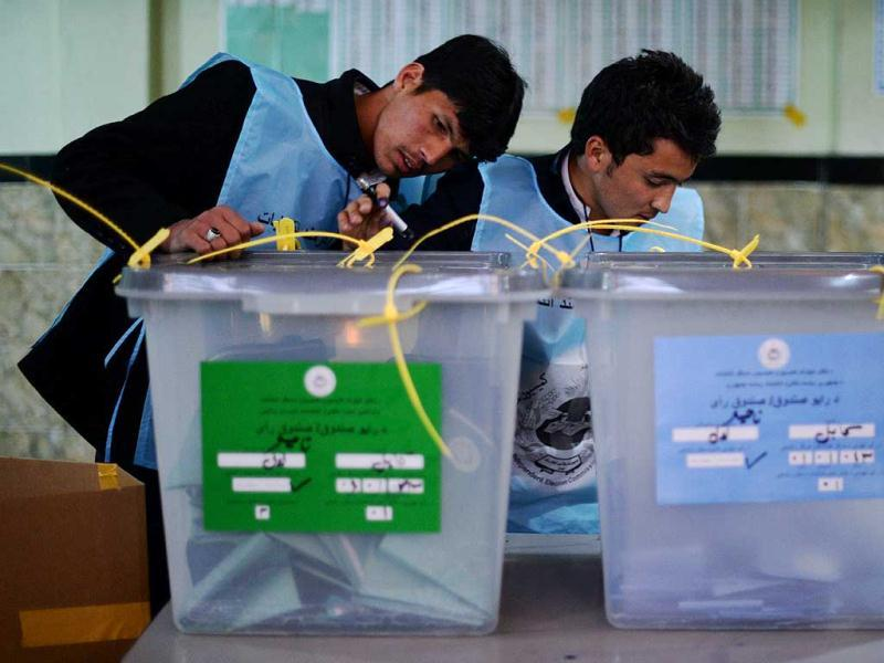 Election workers look at the markings on ballot boxes before opening them and sorting votes out at a polling station after it closed in Kabul. (AFP Photo)