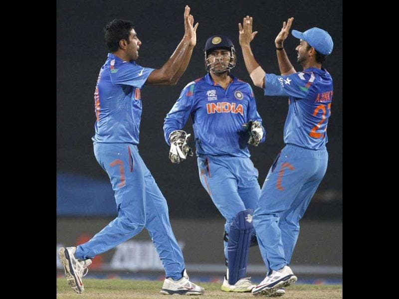 Ravichandran Ashwin (L) celebrates with MS Dhoni (C) and Ajinkya Rahane (R) the wicket of Sri Lanka's Tillakaratne Dilshan during their ICC WOrld Twenty20 match in Dhaka. (AP Photo)