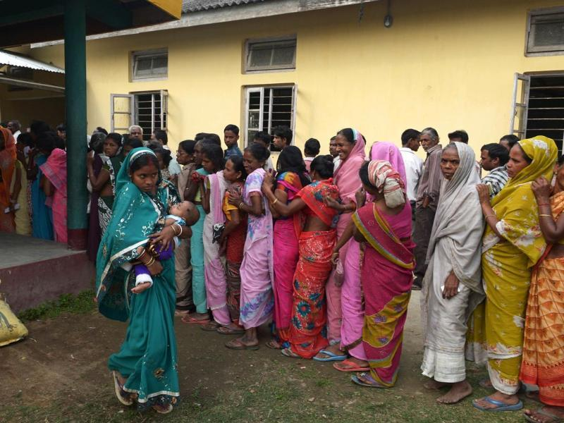 Voters wait in line outside a polling station in Dibrugarh during Lok Sabha elections. (AFP photo)