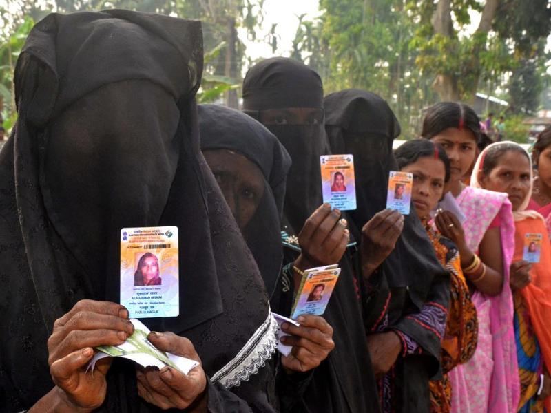Voters pose with identification as they wait in line to vote outside a polling station in Koliabor, Assam. (AFP photo)