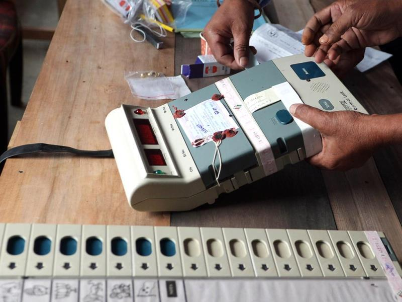 Election Commission officials seal an Electronic Voting Machine (EVM) prior to the start of voting at a polling station in Dibrugarh, Assam. (AFP photo)