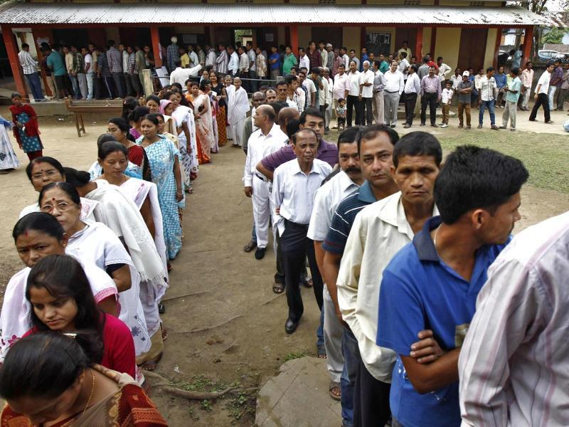 Voters line up to cast their vote outside a polling station in Nakhrai village in Tinsukia district in Assam. (Reuters photo)