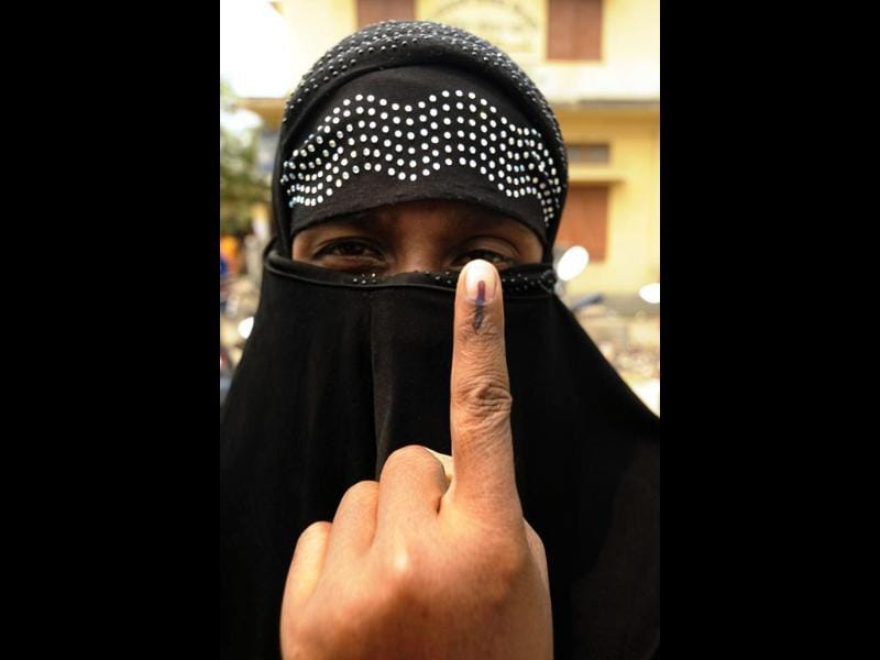 A voter shows her ink-marked finger after after casting her ballot at a polling booth at Pachmile village, in Assam. (AFP photo)