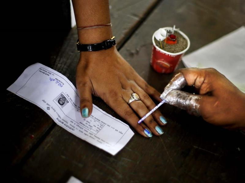 An election officer applies an indelible ink mark on the finger of a woman during the first phase of elections in Dibrugarh, Assam. (AP Photo)