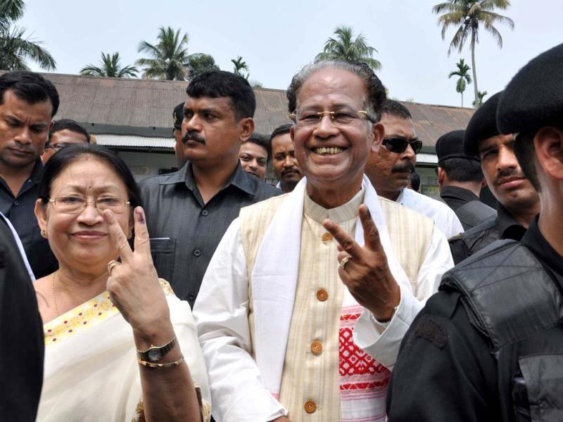 Assam chief minister Tarun Gogoi (C), accompanied by his wife Dolly (L) pose with their ink-stained fingers after having cast their votes in Jorhat some 310 kms east of Guwahati. (AFP photo)
