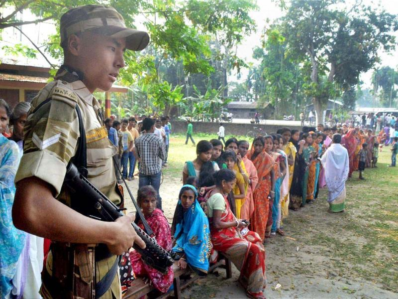 Security guard keeping vigil as women queue up to cast their vote, outside a polling center at Koliabor in Nagaon district of Assam. (PTI Photo)