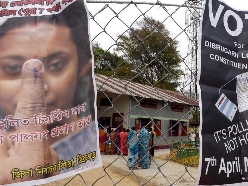 Vote awareness placards are seen on a fence as voters wait in line outside a polling station in Dibrugarh. (AFP photo)