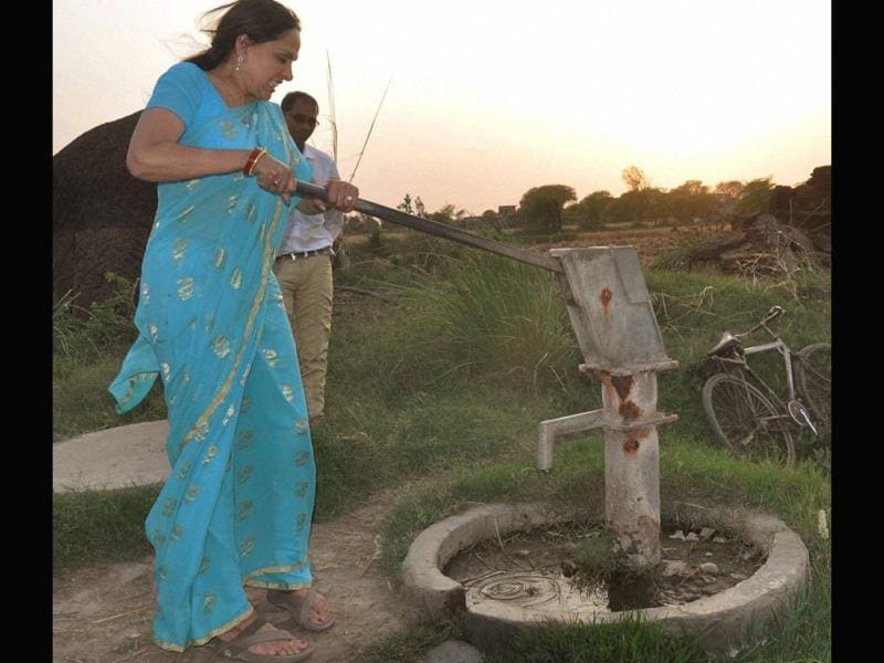 Bollywood actress and BJP candidate Hema Malini operates a hand pump at a village during her election campaign in Mathura. (PTI Photo)