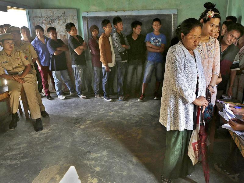 People stand in line to cast their votes inside a voting center at Senapati, in Manipur (AP Photo)
