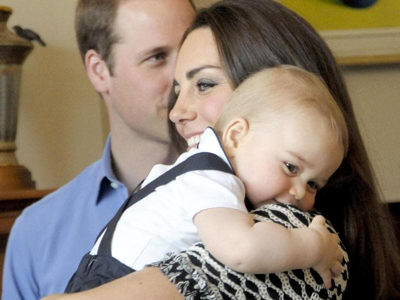 Prince George is held by his mother, Catherine, the Duchess of Cambridge, as Prince William looks on, during a Plunket nurse and parents group visit at Government House in Wellington. (AFP photo)