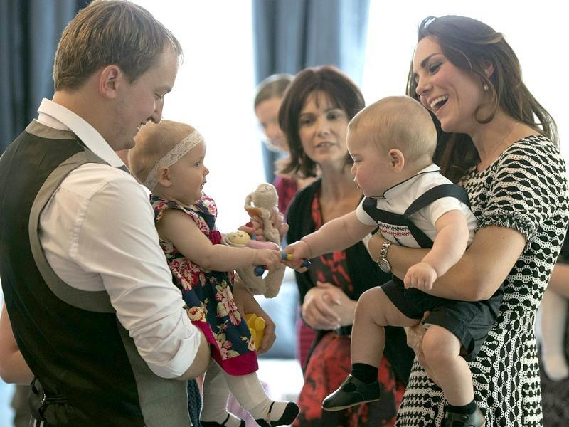 The Duchess of Cambridge holds her son, Prince George, as he plays with a girl during their visit to the Plunket nurse and parents group in Wellington. (AFP photo)