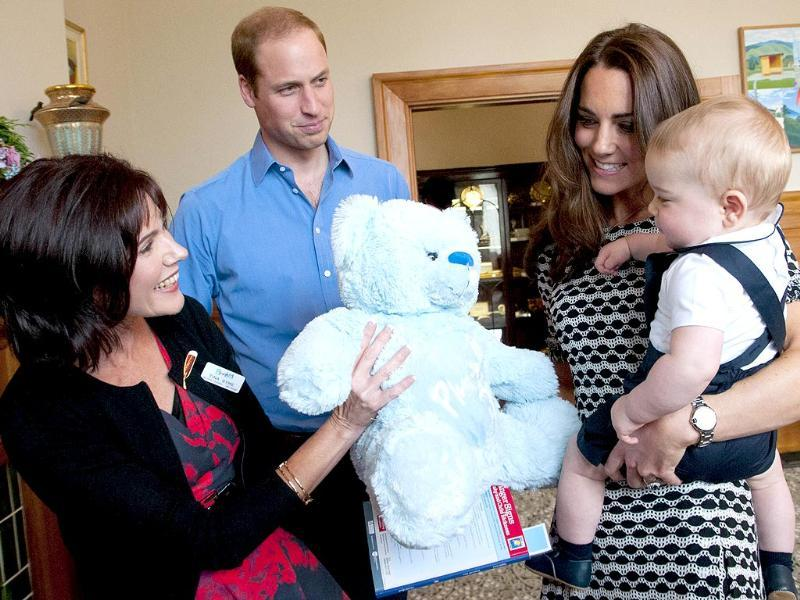 Prince George gets a large soft bear as a gift from Plunket's area manager, Tina Syme (L) during his visit to the Plunket nurse and parents group in Wellington. (AFP photo)