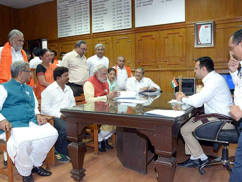 BJP candidate from Vadodara, Narendra Modi goes through his nomination papers before handing it over to collector Vinod R Rao at Vadodara. (HT Photo)