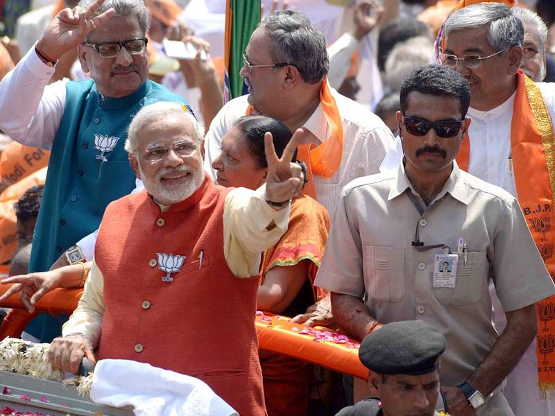 BJP candidate from Vadodara, Narendra Modi flashes the victory sign during a road show before filing his nomination papers. (HT Photo)