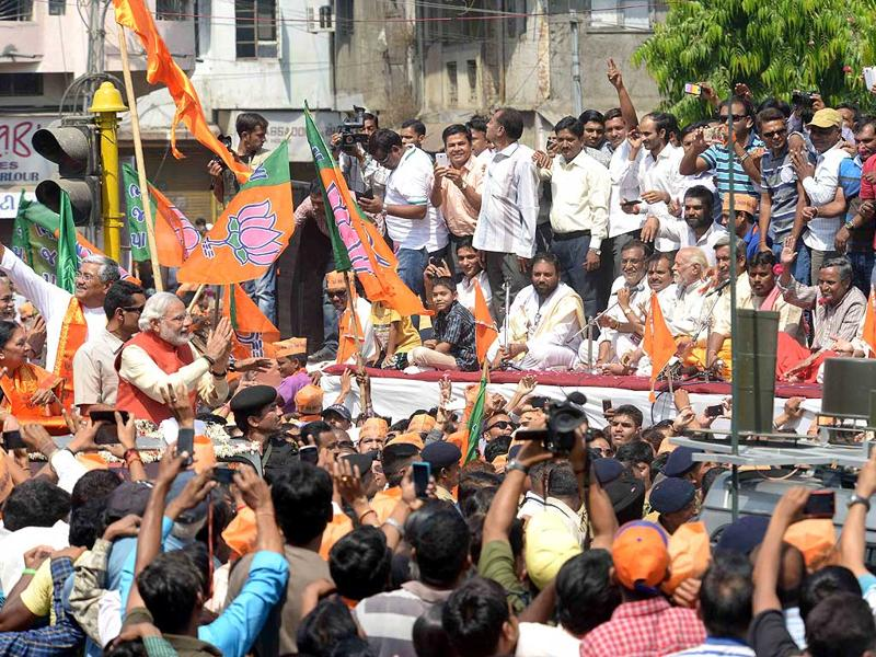 BJP prime ministerial nominee Narendra Modi waves to the crowd assembled for his road show prior to filing his nomination papers at Vadodara. (HT Photo)