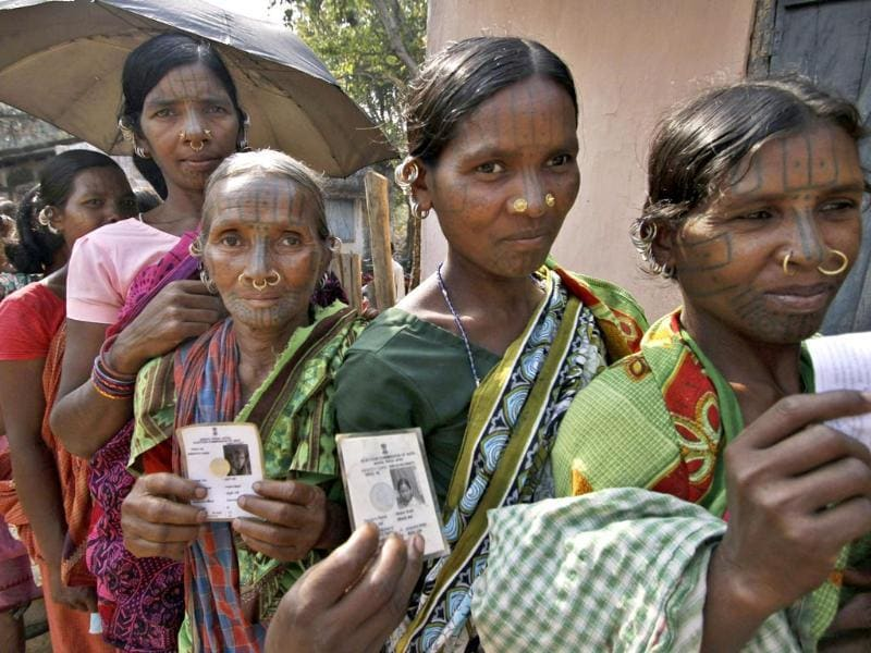 Indigenous women belonging to the Kandha tribe display their voter's identity cards as they wait to cast their votes outside a polling station during parliamentary elections at Dingesiguda village in Kandhamal district, Orissa. (AP Photo)