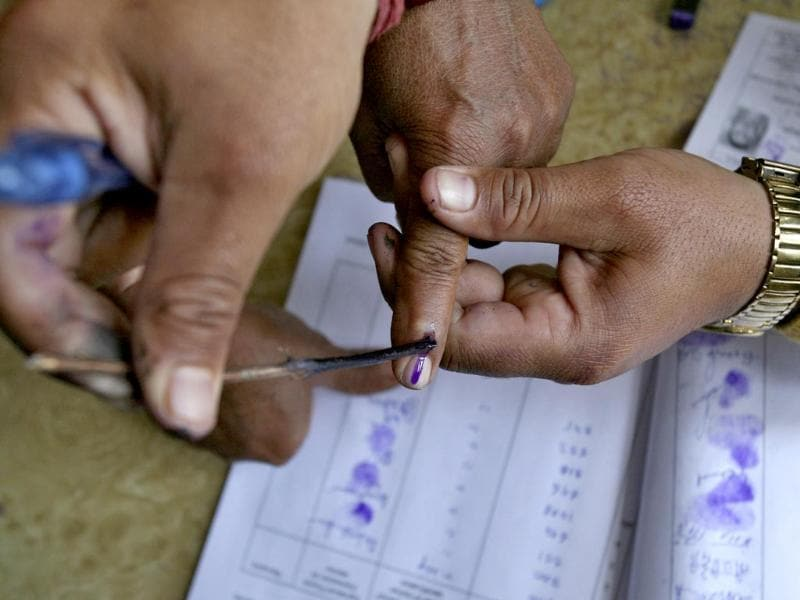 A polling officer applies ink on the finger of a voter at a polling station on the outskirts of Jammu. (Reuters Photo)