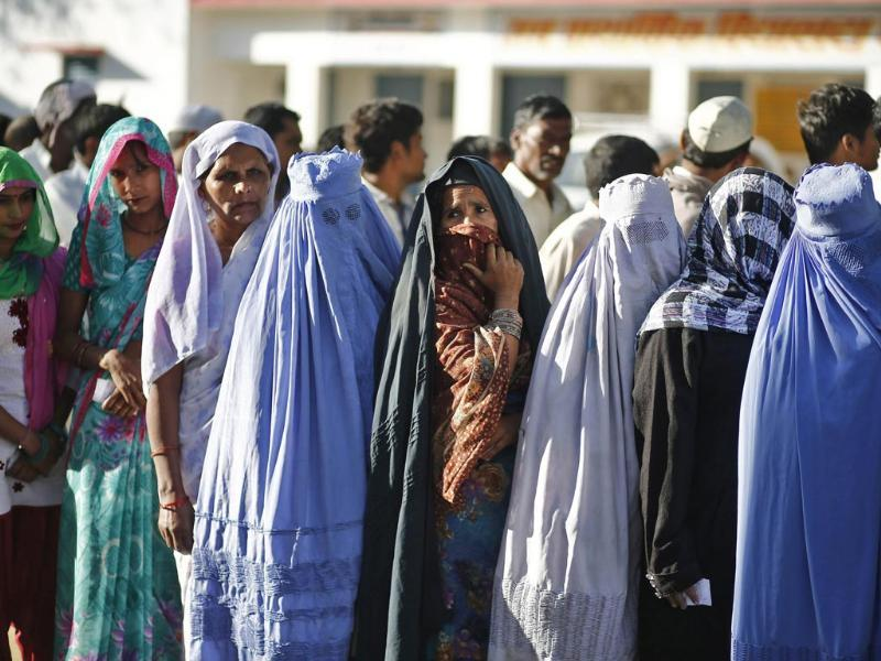 Muslim women, who were displaced by deadly religious strife last year, stand in a queue to cast their votes for the general election at a polling station in Palra village in Muzaffarnagar district in Uttar Pradesh. (Reuters Photo)