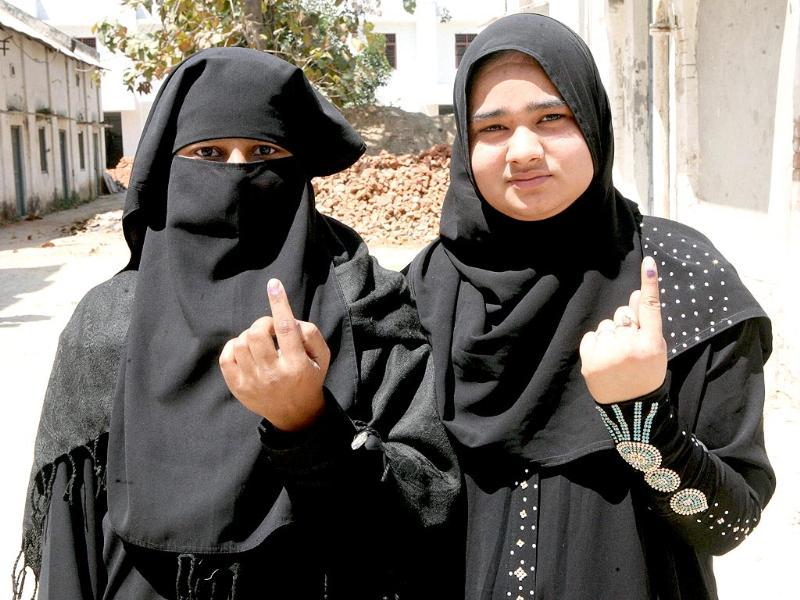 Women show their voter ID card after casting their vote in the Lok Sabha election in Aligarh. (PTI Photo)