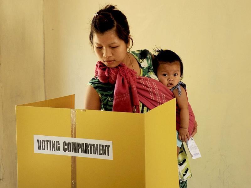 A voter holds a child as she casts her ballot at a polling station at Bungthuam, on the outskirts of Aizwal, in Mizoram. (AFP photo)