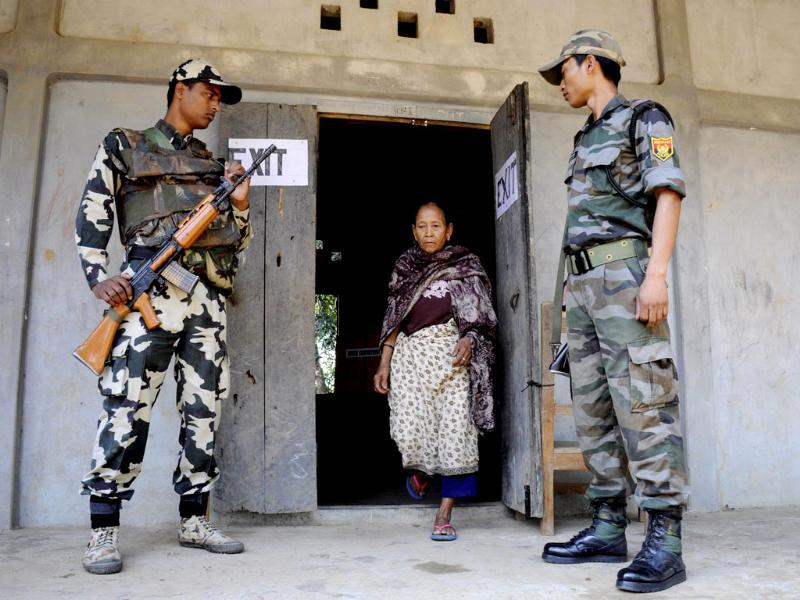 Security personnel look on as a voter leaves a polling station after casting her ballot in Kahnmun in Mizoram. (AFP photo)