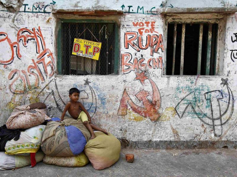 A child sits on sacks filled with clothes in front of graffiti showing the Communist Party of India-Marxist (CPI-M) party symbol at a secondhand cloth market in Kolkata. (Reuters Photo)