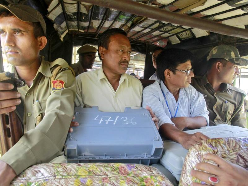 Security personnel sit in a vehicle next to the polling officers (in plain clothes) carrying electronic voting machines (EVM) from a distribution centre ahead of the fourth phase of general election in Tripura. (Reuters Photo)