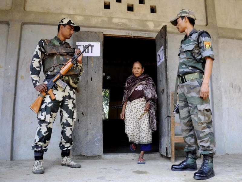 Security personnel look on as a voter leaves a polling station after casting her ballot in Kahnmun, Aizwal, the capital of Mizoram. (AFP Photo)