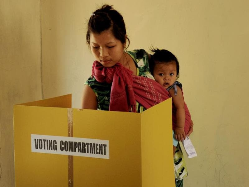 A voter holds a child as she casts her ballot at a polling station at Bungthuam, Aizwal, the capital of Mizoram. (AFP Photo)
