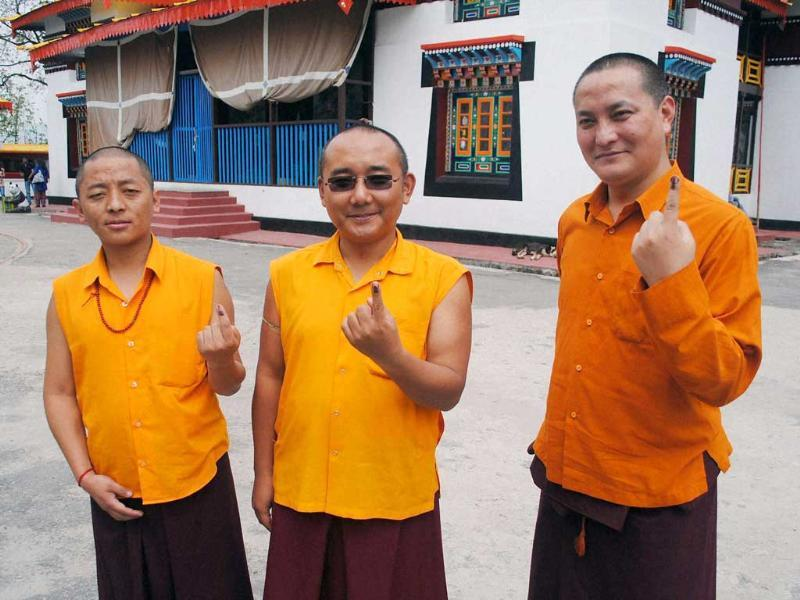 Monks showing their ink marked fingers after casting votes for Lok sabha polls at Enchey Monastery in Gangtok. (PTI photo)