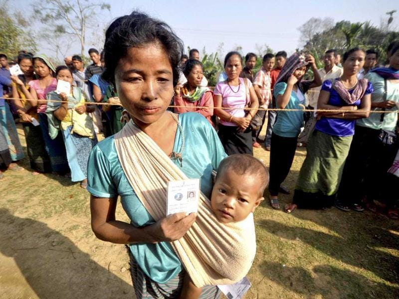 A woman voter carries her kid as others wait to cast votes for Tripura West Lok Sabha polls outside a polling station in Dhamcherra. (PTI photo)