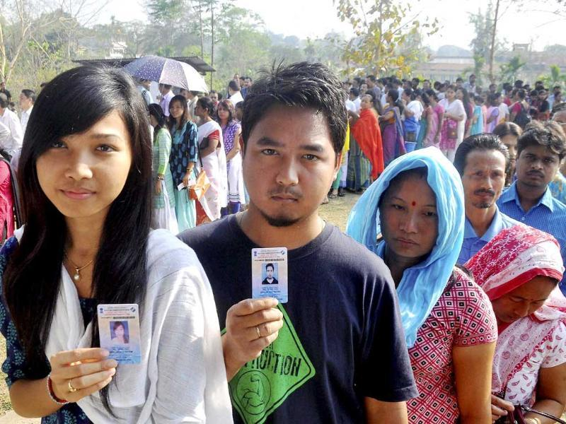 People show their voter identity cards as they wait in queues to cast their votes for Lok Sabha polls at a polling station, at Diphu in Karbi Anglong district of Assam. (PTI photo)
