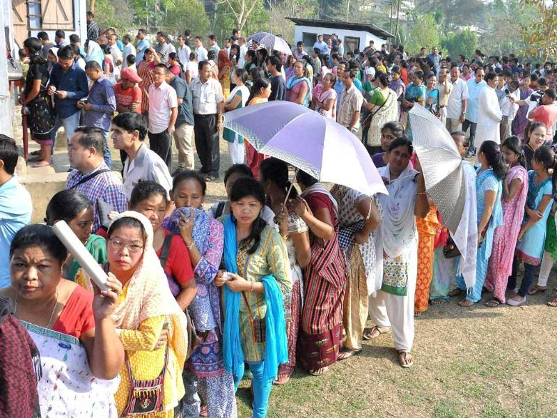 People wait in queues to cast their votes for Lok Sabha polls at a polling station, at Diphu in Karbi Anglong district of Assam. (PTI photo)