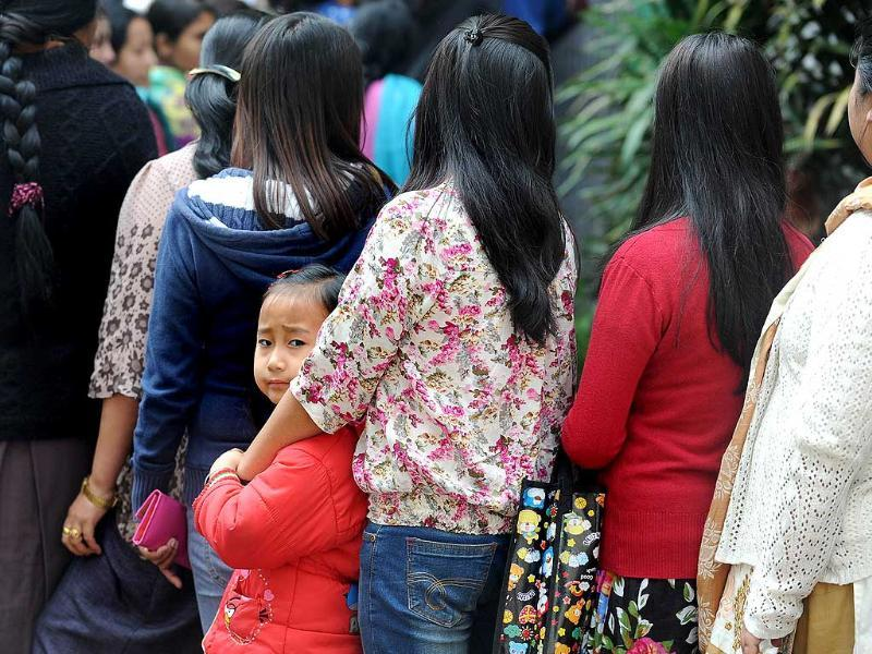A child looks on as Sikkimese voters queue to cast their ballot at a polling station in Gangtok, in Sikkim. (AFP photo)