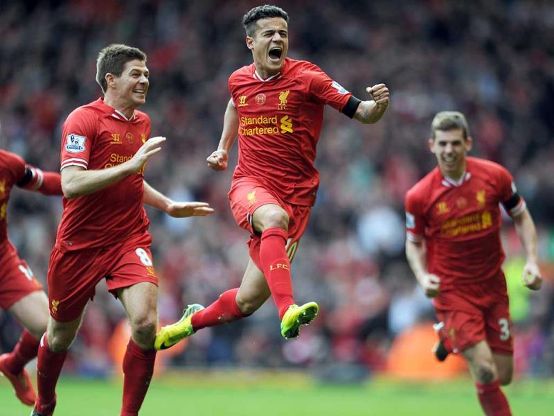 Liverpool's Philippe Coutinho, centre, celebrates with teammate Steven Gerrard, left, after he scored the third goal of the game for his side during their English Premier League soccer match against Manchester City at Anfield in Liverpool, England. (AP Photo)