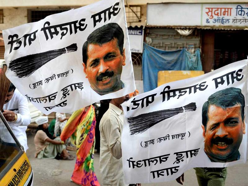 Aam Aadmi Party (AAP) supporters gather with banners outside the party office before an election roadshow in Mumbai. (AFP Photo)